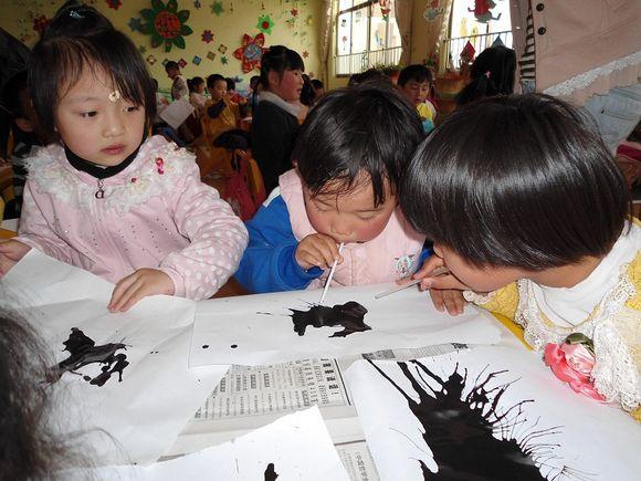 幼儿在画面上练习吹画梅花.